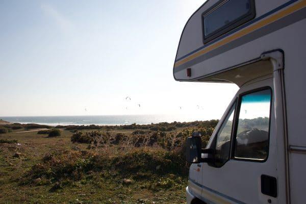 Ein Wohnmobil schaut auf's Meer im Hintergrund viele Kite