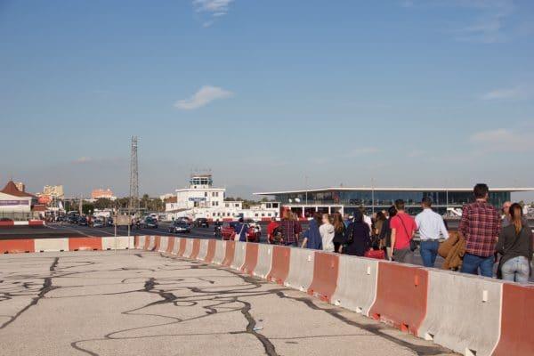Viele Menschen und Autos überqueren das Flugfeld in Gibraltar