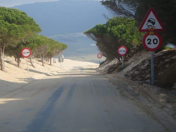Straße mit Warnschildern und viel Sand