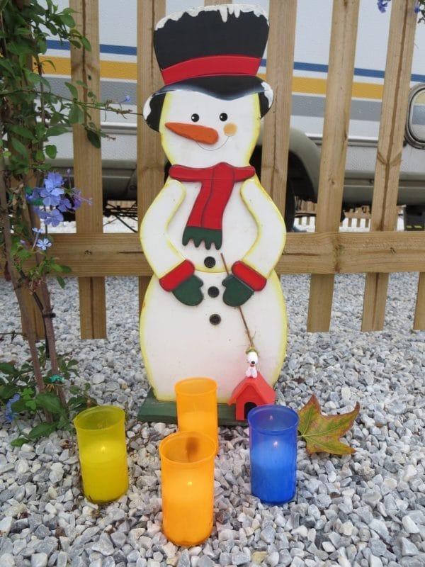Ein Schneemann aus Holz vor einem Holzzaun auf hellem Kies, davor vier Windlichter