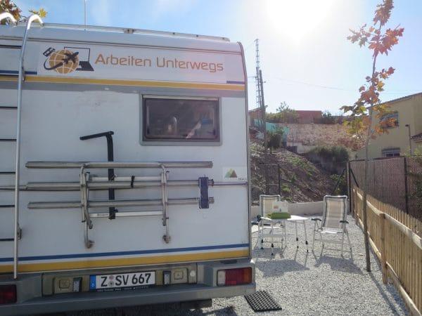 Ein Wohnmobil von hinten daneben Stühle und ein Tisch und Sonne von vorne