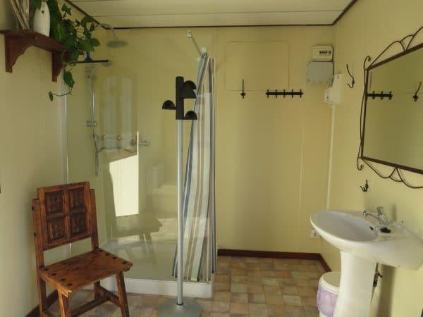 Ein Raum mit einer großen Dusche, einem Stuhl und einem Waschbecken