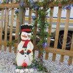 Ein Zaun mit einer blühenden Rankpflanze und einem Holzschneemann