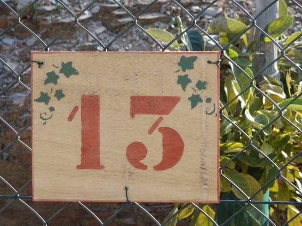 Ein Schild mit der Zahl 13 und ein paar Weinranken