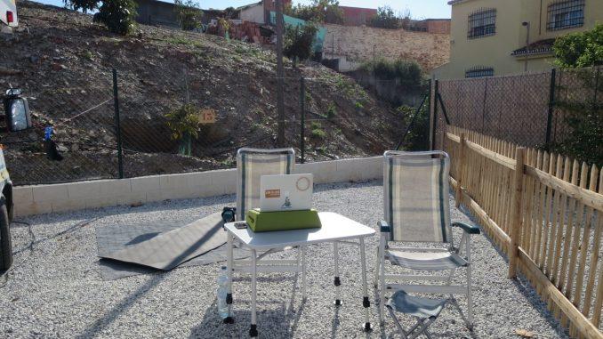 Tisch, Stühle und eine Yogamatte neben einem Wohnmobil