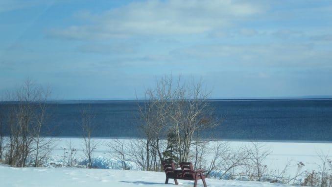 Eine einsame Bank auf einer schneebedeckten Wiese vor einem See