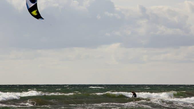 Ein Kitesurfer vor grauen Wolken