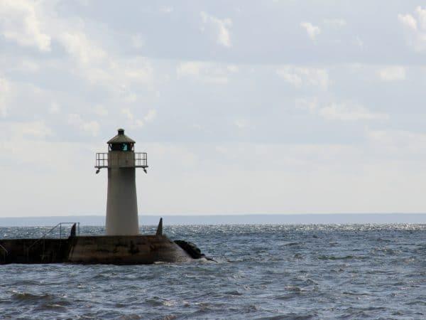Ein Leuchtturm und um ihn herum See und Wolken