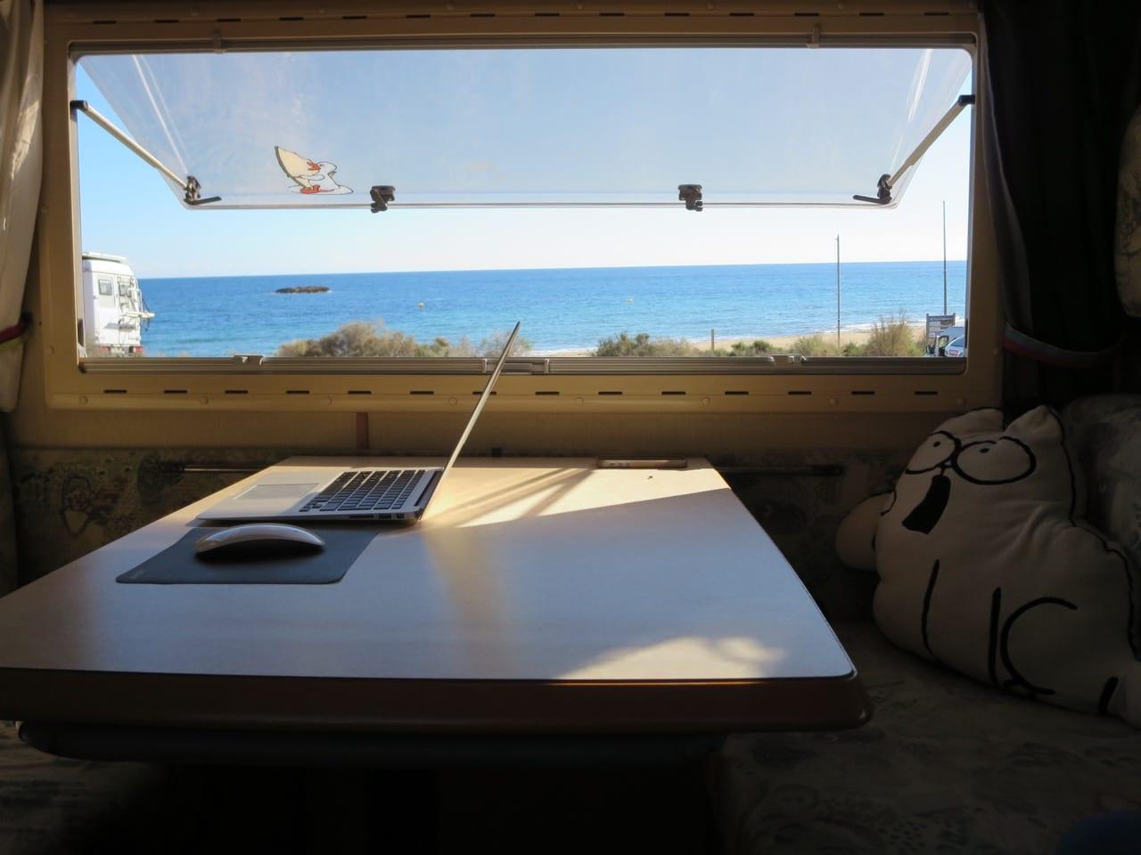 Ein Laptop steht auf einem Tisch vor einem Fenster mit Blick aufs Meer