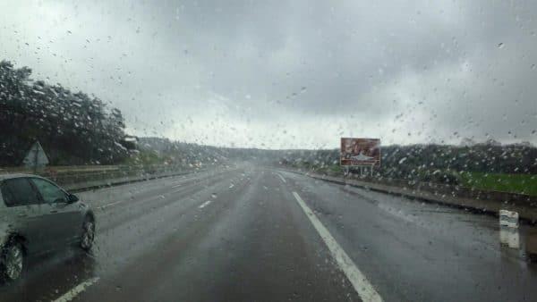 Eine regennasse Autobahn aus einer Scheibe mit Regentropfen heraus fotografiert
