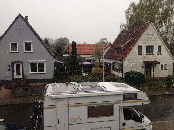 Ein Wohnmobil steht in einer Straße vor zwei Häusern, draußen schneit es