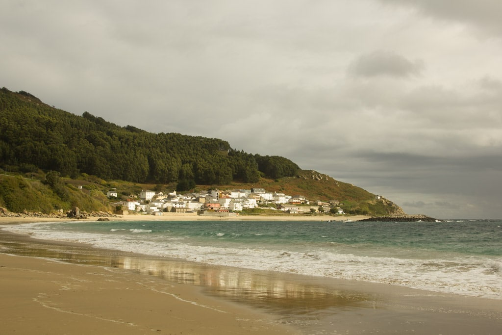 Blick über den Strand und das Meer auf ein kleines Örtchen vor einem bewaldeten Hügel