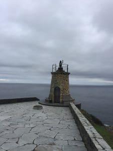 Ein kleiner alter Leuchtturm am Ende eines steinernen Weges
