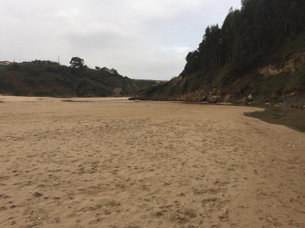 Blick über einen Sandstrand auf die Flußmündung zur Bucht