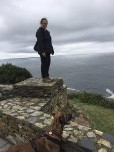 Eine Frau steht auf einer steinernen Erhöhung vor ihr ein Hund