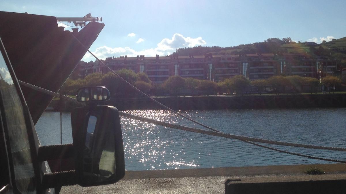Blick aus einem Wohnmobil auf einen Hafen mit einem großen Schiff, Häusern und dahinter Berge