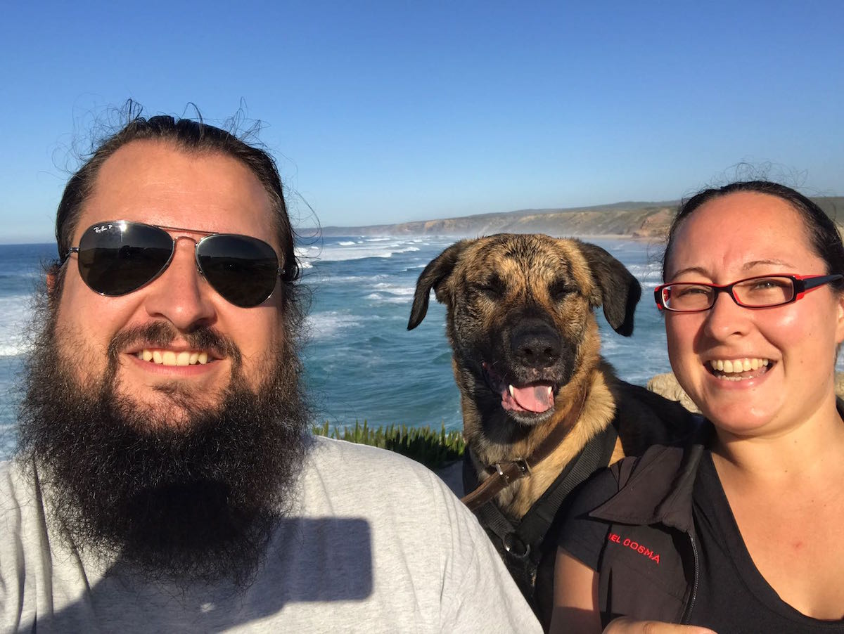 Selfie von einem glücklichen Päarchen in der Mitte ein Hund hinter ihnen das Meer