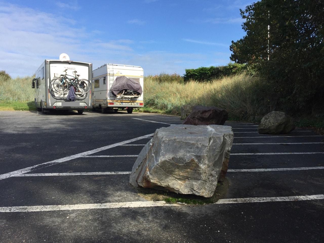 Im Vordergrund ein Stein, im Hintergrund zwei neben einander stehende Wohnmobile vor einer Düne.